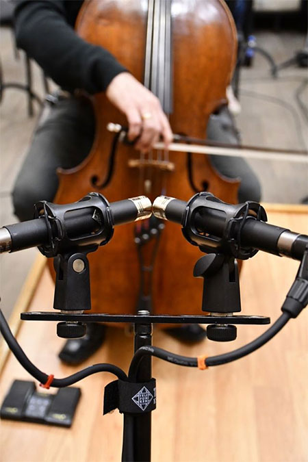 cello player being recorded for radio broadcast
